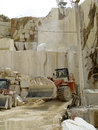 Marble quarry excavators working for the transport of white cut into blocks Stock Photography