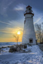 Marblehead lighthouse sunrise the historic in northwest ohio sits along the rocky shores of lake erie seen here at in winter with Stock Image