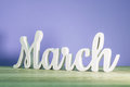 March - biginning of springtime concept. Wooden carved inscription on purple or dark pink background