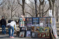March new york city tourists browse a vendor s art di colorful display of posters and paintings in nyc central park Royalty Free Stock Photography