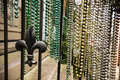 Mardi gras beads colorful collections of bead hanging from a rail with a fleur de lis Stock Photo