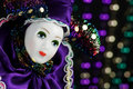 Mardi gras marionette mask a porcelain female or with purple green and gold bokeh on black background Stock Image