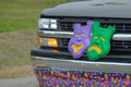 Mardi gras parade the front of a pickup truck is decorated with tragedy comedy masks and a banner during a celebration in Stock Photography