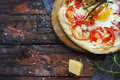 Margarita pizza with basil leaves and egg on wooden table, top v