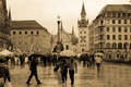 Marienplatz and the old city hall munich germany people walking in rain in altes rathaus in background Royalty Free Stock Photo