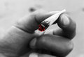 Marijuana joint closeup of a hand holding a lit cigarette cannabis half smoked color drop out lit end of colored red s photo with Royalty Free Stock Photos