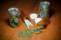Marijuana on table a wood in piles jars prescription bottles and rolled into joints Royalty Free Stock Photography