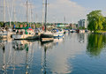 Marina with boats reflecting in the water a city background and masts of boat are Royalty Free Stock Photography