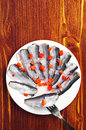 Marinated salted fish with carrots in a plate on wooden table top view Stock Images