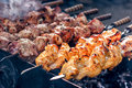 Marinated shashlik preparing on a barbecue grill over charcoal. Shashlik or Shish kebab popular in Eastern Europe.