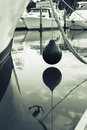 Marine buoy hanging above water between moored boats in Tutukaka Royalty Free Stock Photo