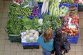 Market fruit and vegetable customers browse goods displayed on stall inside an indoor in rome italy Stock Photo
