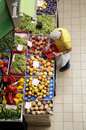 Market fruit and vegetable elderly customer browses goods displayed on stall inside an indoor in rome italy Stock Photos