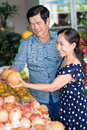 At the market vertical image of senior family couple choosing fresh fruits on foreground Stock Photography