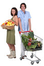 Market vs supermarket couple shopping for fruit and vegetables Stock Photos