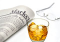Markets newspaper with whiskey and glass ice on white background shallow depth of field Stock Photos
