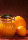Marmalade jar a with a n orange and a clementine on the side shot in a studio on a texturised reddish brown backdrop Royalty Free Stock Image