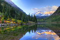 Maroon bells reflection of snowcapped in fall at sunrise Stock Images
