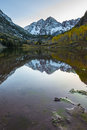 Maroon bells sunrise aspen colorado vertical and its reflection in the lake with fall foliage in peak at Royalty Free Stock Photos