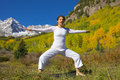 Maroon bells yoga instruction a woman teaching in the scenic colorado mountains in fall Royalty Free Stock Images