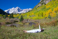 Maroon bells yoga a woman practicing at the scenic aspen colorado in fall Stock Images