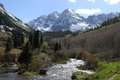 Maroon creek spring time filled with melt water rushing down from the side of famous bells mountains part of elk mountain Stock Photo