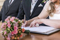 Marriage elegant bride signing register, holding pen and official document wedding couple Royalty Free Stock Photo