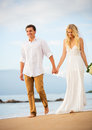 Married couple bride and groom holding hands at sunset on beaut beautiful tropical beach in hawaii Royalty Free Stock Photos