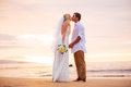 Married couple bride and groom kissing at sunset on beautiful tropical beach in hawaii Royalty Free Stock Images