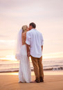 Married couple bride and groom kissing at sunset on beautiful tropical beach in hawaii Stock Photo