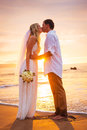 Married couple bride and groom kissing at sunset on beautiful tropical beach in hawaii Stock Photos