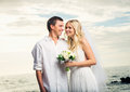 Married couple bride and groom at sunset on beautiful tropical beach in hawaii Stock Photography