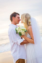 Married couple bride and groom at sunset on beautiful tropical beach in hawaii Royalty Free Stock Photography