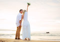 Married couple bride and groom at sunset on beautiful tropical beach in hawaii Royalty Free Stock Image