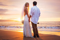 Married couple bride and groom at sunset on beautiful tropical beach in hawaii Stock Image