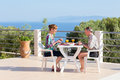 Married couple eating at table on terrace near sea Royalty Free Stock Photo