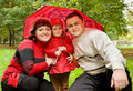 Married couple and girl with umbrella in park Royalty Free Stock Images