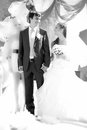 Married couple holding hands under decorative arch black and white full length portrait of happy just Stock Photo