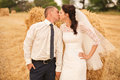 Married couple kissing near haystack on field Royalty Free Stock Photos