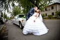 Married couple kissing on road in front of car newly Royalty Free Stock Photography