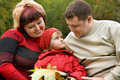 Married couple and little girl sit in park, autumn Stock Photography