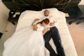Married couple lying on big bed at hotel newly Royalty Free Stock Images