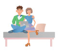 Married couple, man and woman sitting on bed with laptop.
