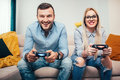 Married couple playing video games on general gaming console. Details of modern lifestyle with couple having fun