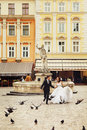 Married couple run across the citysquare full of pigeons Royalty Free Stock Photo