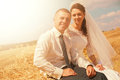 Married couple sitting on haystack at sunny day bright Royalty Free Stock Image