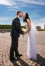 Married couple standing in front of each other on paving road and bending to kiss Stock Photo