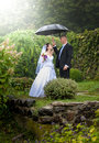 Married couple standing under umbrella at park just Stock Photo