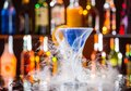 Martini drink served on bar counter with dry ice smoke effect with blur bottles background Stock Photos