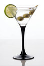 Martini glass and alcohol with green olives Royalty Free Stock Photo